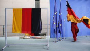 A staff member prepares German flags . REUTERS RTX1RFTQ