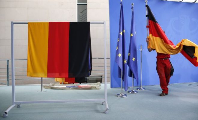 A staff member prepares German flags . REUTERS RTX1RFTQ